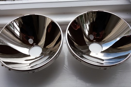 Actual photo of a pair of Porsche headlamp reflectors resilvered by Ashford Chroming.